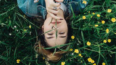 meisje ligt in grasveld