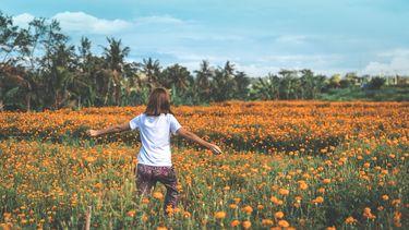 meisje loopt in bloemenveld