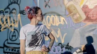 Vrouw met gekleurd haar staat voor een muur met graffiti