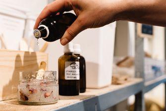 hand schenkt olie in potje