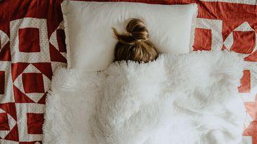 vrouw ligt ziek in bed